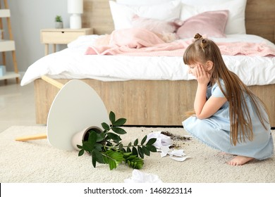 Little girl in room with dropped houseplant and paper pieces on carpet