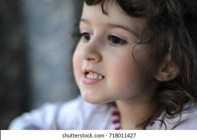 the little girl in the room on the window playing with the toys . the light from the rising sun fills the room