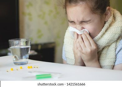 little girl in a room in a scarf with a throat wound with a temperature and a thermometer, sneezing and drinking cough medicine