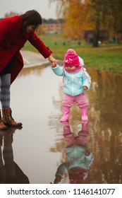 little girl with rubber boots in puddle
