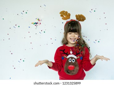 Little girl in rudolf hat celebrating for a Christmas on white background. Merry Christmas and Happy Holiday.