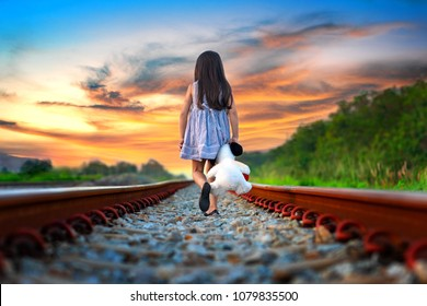 little girl run away from home, walking on railway alone, upset with parent and disappoint mind, sadly walikng with dollmate