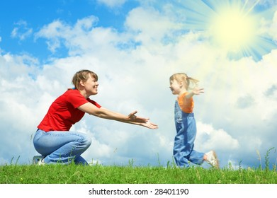 little girl run to mother embrace on green grass under sky with clouds