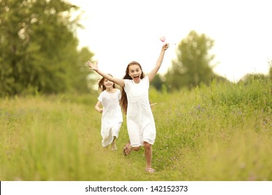 Little girl running around on the field with wild flowers