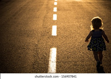 Little girl running away on the road ahead