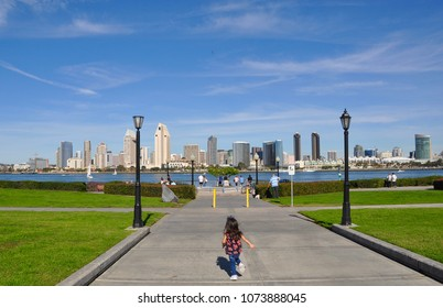 Little girl running away with the view of San Diego skyline in backdrop