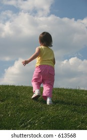 Little girl running up a hill.