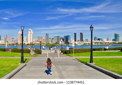 Little girl running in a hot summer day with buildings in the horizon