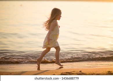 little girl running on the beach in the sunset light