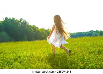 Little girl running on green grass. Beautiful warm summer evening.