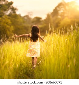Little girl running on meadow with sunset