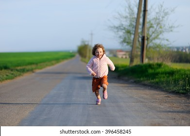 Little girl running on a meadow in a field. Happy child, kid playing and having fun outdoors in summer.