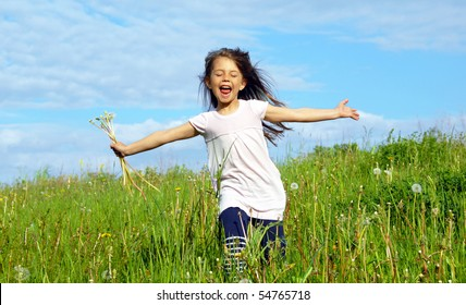 Little girl running on the meadow, holding dandelions, she is really happy