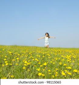 Little girl running on a meadow in a field of flowers, dandelions
