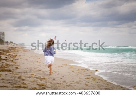 a9ecabede3 Little girl running on the ocean beach on a cloudy day. Vacation by the sea