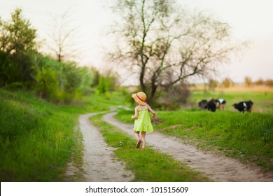Little girl running on the road. Nature background with cows.