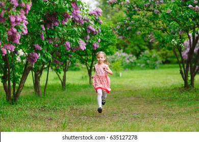 A little girl is running in the park.