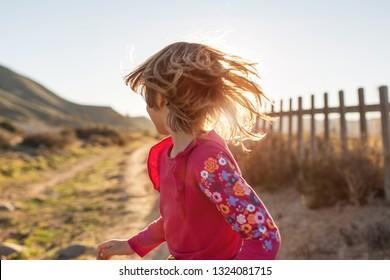 Little girl running through the Spanish landscape, Rambla del Playazo, Cabo de Gata - Nijar Natural Park, Spain