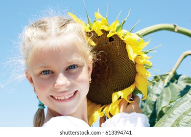 Little girl in a rustic dress with a sunflower