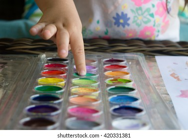 little girl 's finger touching water paints on glass table