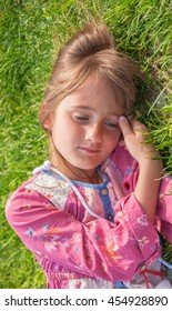 Little girl with a sad expression on his face romantic on the lawn