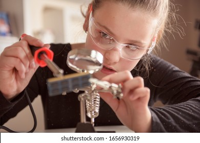 Little girl with safety glasses works with a soldering iron on a computer component