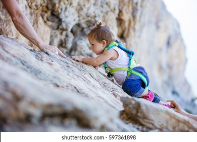 Little girl in safety harness climbing up cliff, mom and dad safeguarding her from above and beneath