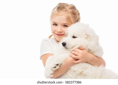 Little girl with a samoyed puppy