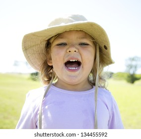 A little girl with sand on her face laughing out loud