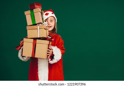 Little girl in santa claus dress holding a pile of gift boxes. Kid dressed as santa carrying gifts.