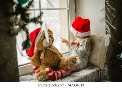 little girl in a Santa Claus hat with teddy bear sitting on the window. The child looks out the window and waiting for Christmas, Santa Claus