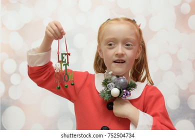 Little girl in a Santa Claus suit holding a Christmas bouquet and a Christmas decoration that reads ' let it snow '