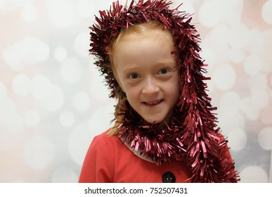 Little girl in a Santa Claus suit being silly with Christmas tinsel wrapping it around her face and smiling on a winter blurred background