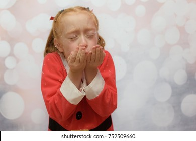 Little girl in a Santa Claus suit blowing snow from out of her hands on a winter background