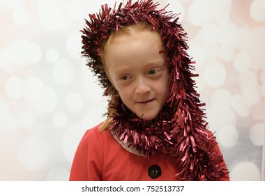 Little girl in a Santa Claus suit being silly with Christmas tinsel wrapping it around her face and smiling but not looking at camera on a winter blurred background
