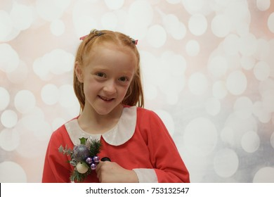 Little girl in a Santa Claus suit holding a Christmas bouquet on a winter blurred background