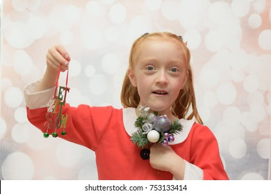 Little girl in a Santa Claus suit holding a Christmas bouquet and a Christmas decoration that reads 'let it snow' on a winter blurred background
