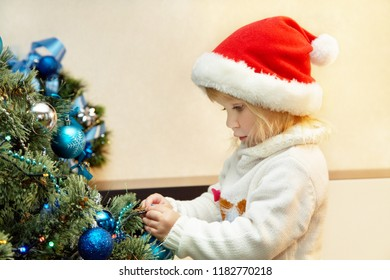 little girl in santa hat decorating a Christmas tree with blue balls