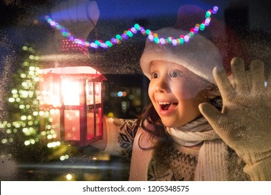 little girl in santa hat and with gifts shines a lantern into the window from winter street