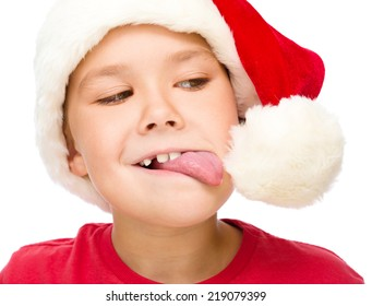 Little girl in santa hat is trying to touch the pompom with her tongue, isolated over white