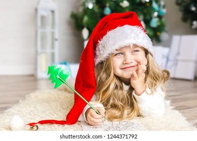Little girl in Santa hat writes letter to Santa Claus