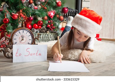 Little girl in Santa hat writes letter to Santa Claus near christmas tree and clock