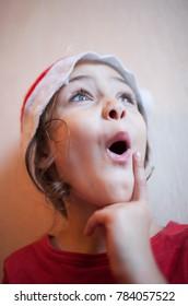 Little girl in Santa's cap grimaces
