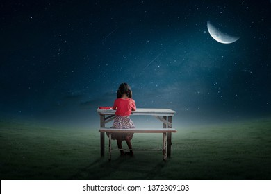 The little girl sat alone reading a book on the half moon night.
