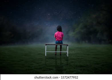 The little girl sat in the chair in the middle of the grass, staring at the stars.