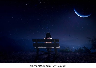 The little girl sat half-frosted in the quiet night on a cliff.