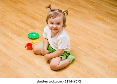 little girl sat on the floor with toy tea things