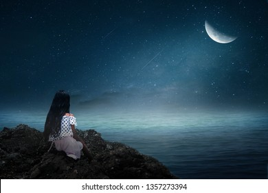 The little girl sat on the rock, looking at the half moon, lonely.