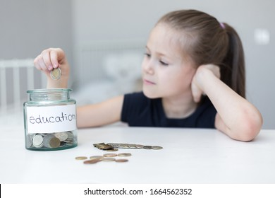 A little girl saves money for education. child counts and puts coins in a glass bottle in her room. The child saves money on the concept of the future
