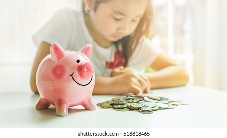 Little girl saving money into piggy bank with pile of coins on table at home.A pink piggy bank are smile and happy while standing on table